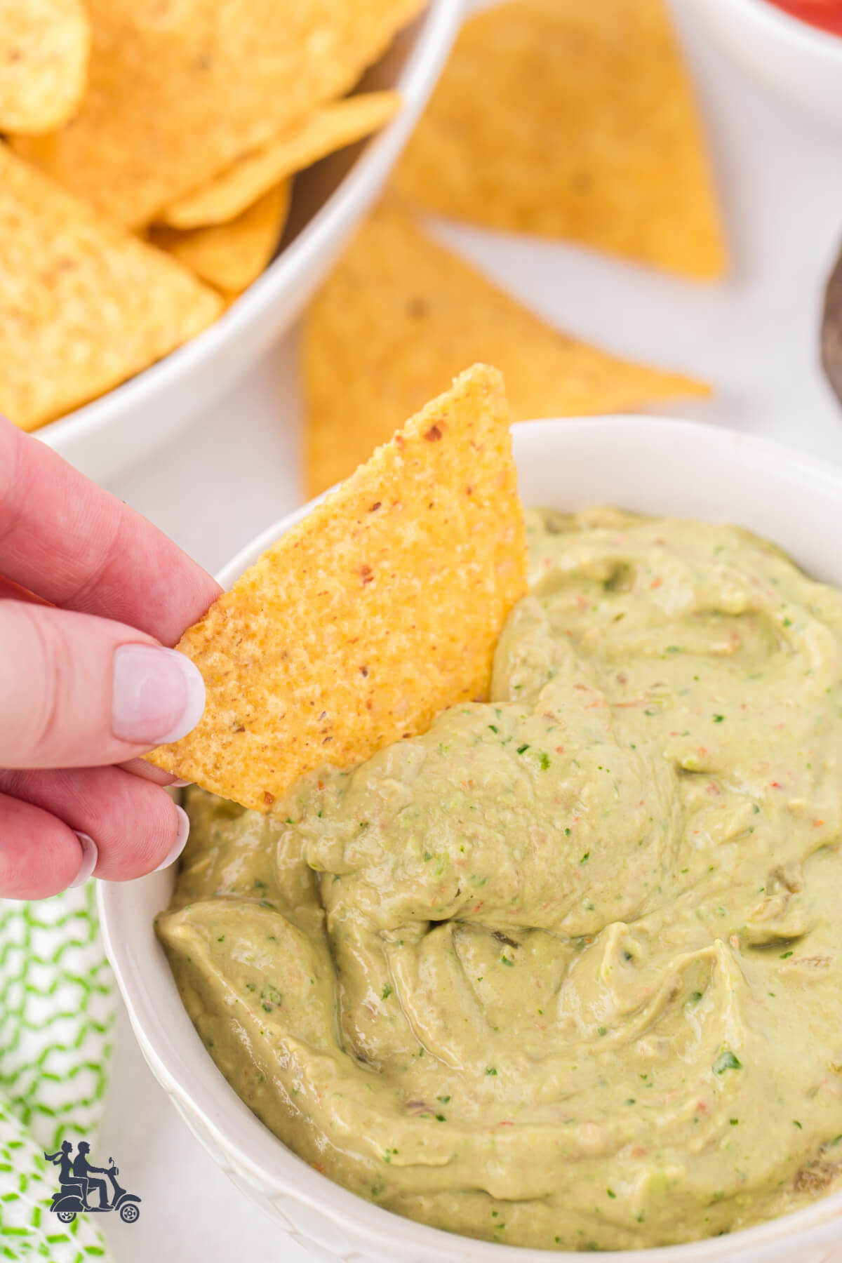 A hand with a tortilla chip dipping into the guacamole salsa.