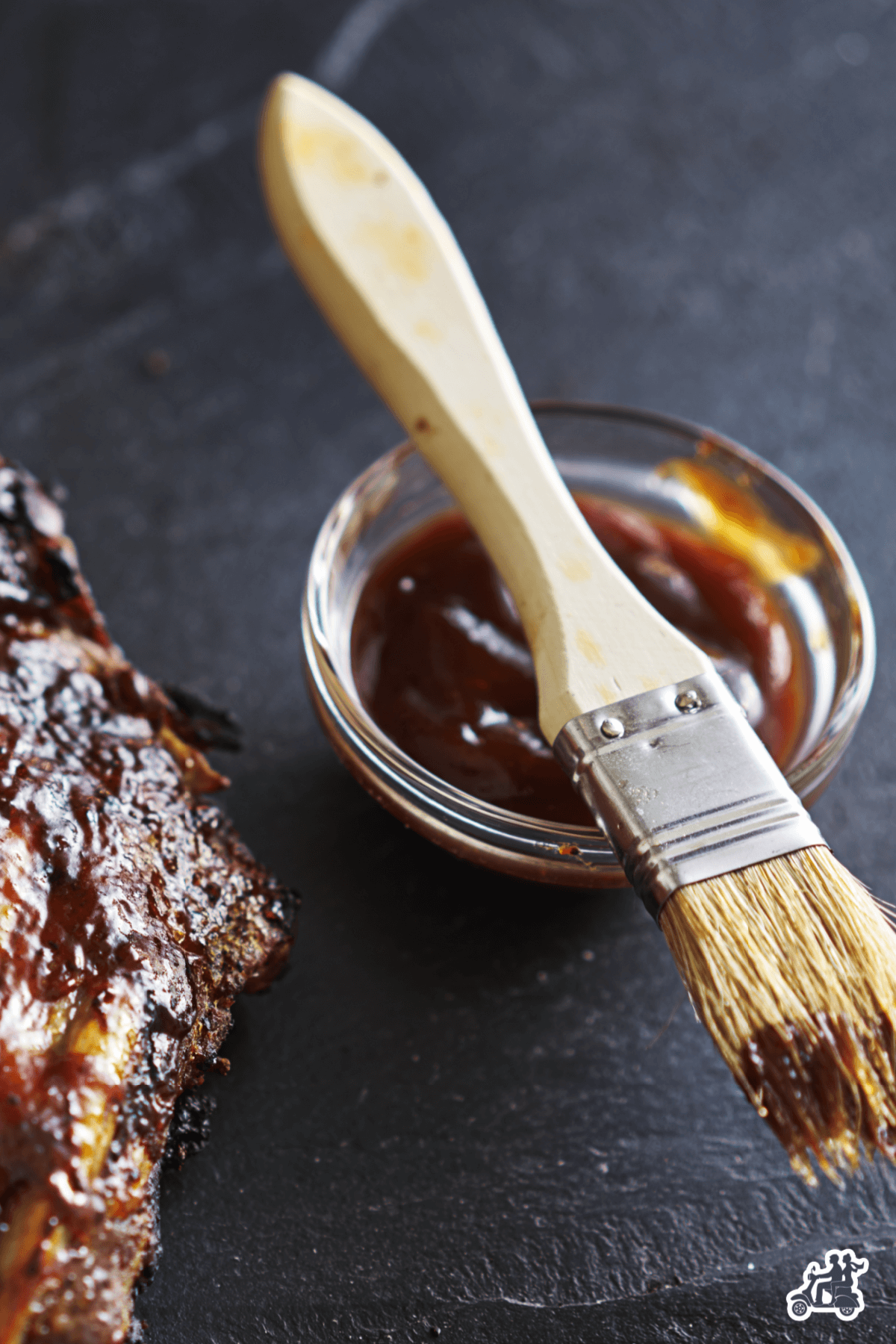 A glass container with Bourbon BBQ sauce and brush for slathering the sauce on meats.