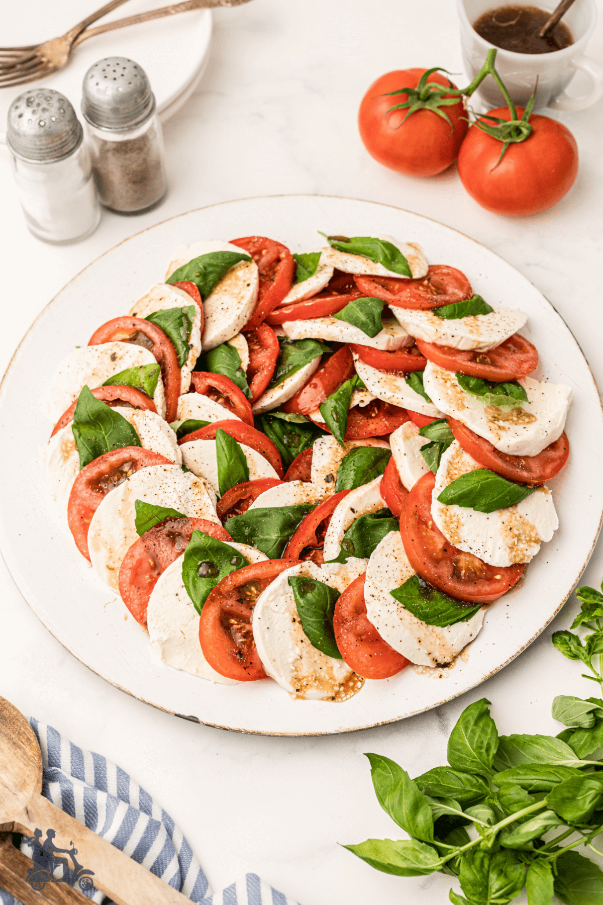 A Caprese Salad on a white platter with the tomatoes, mozzarella, and basil leaves layered in a circle.