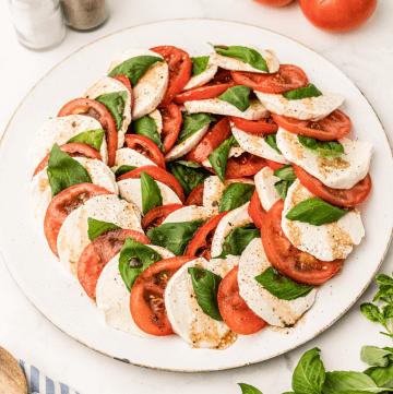 A white platter with Caprese Salad in the red, white, and green of the Italian Flag