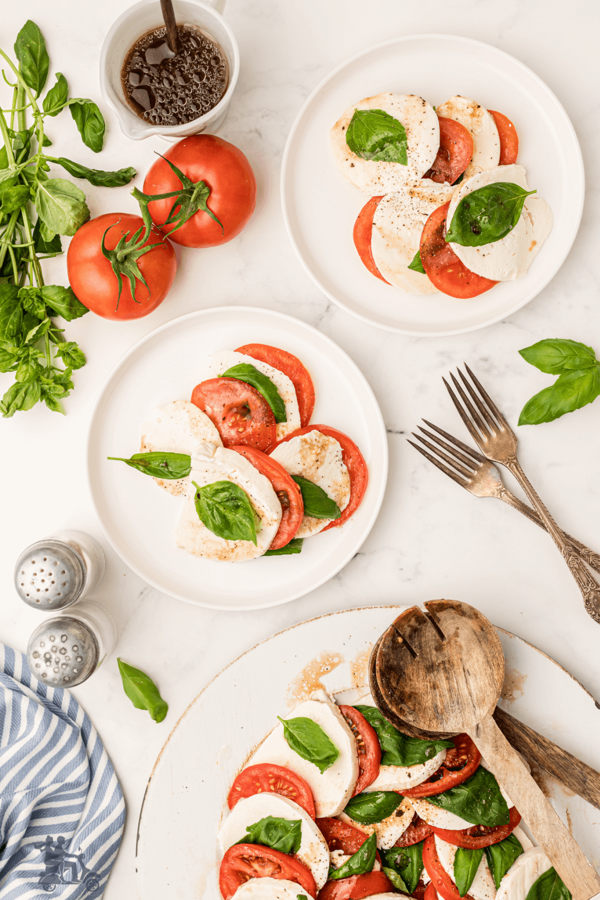 Italian Antipasto Caprese Salad on two salad plates with forks on table ready to eat.