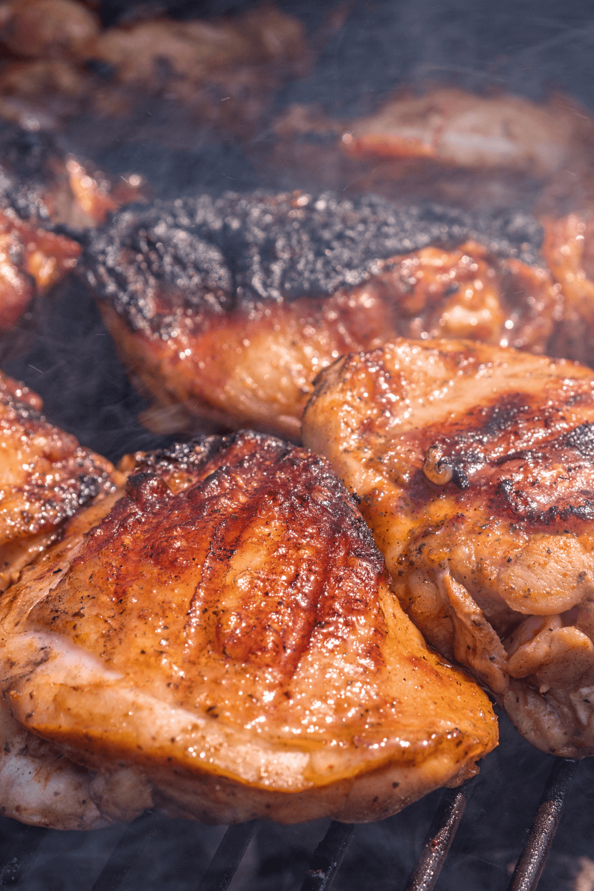 Marinated chicken thighs on grill.