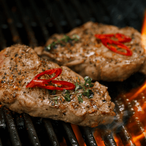 Two steaks on Grill after being marinated.