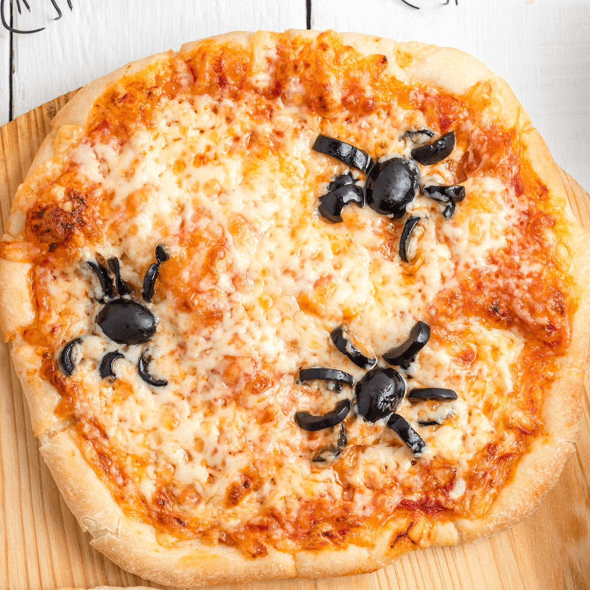 Olive spiders on a mini-pizza for some Halloween fun.