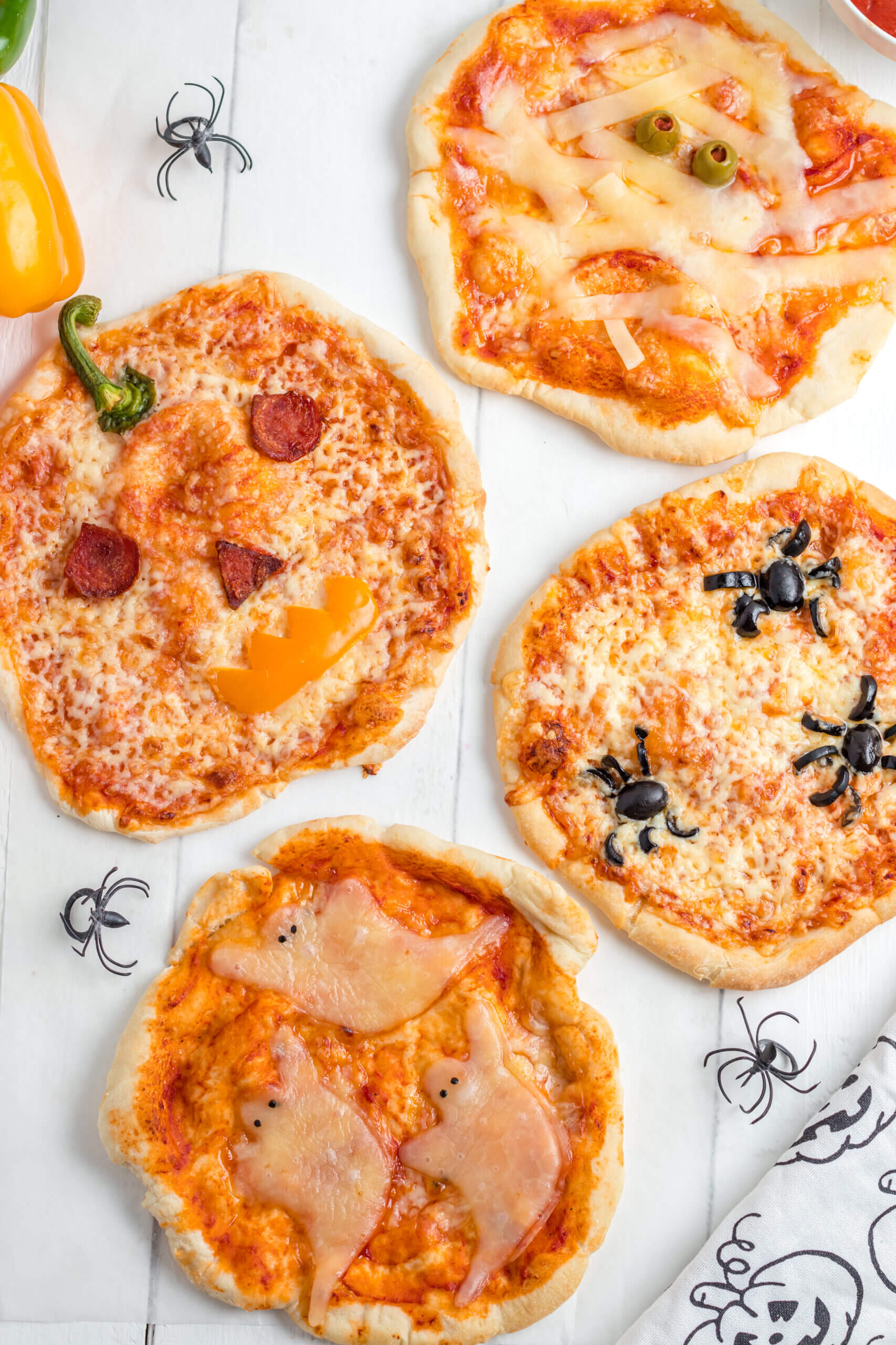 Mini Halloween Pizzas with ghosts, spiders, the the form of a Jack-O-Lantern and a Mummy.