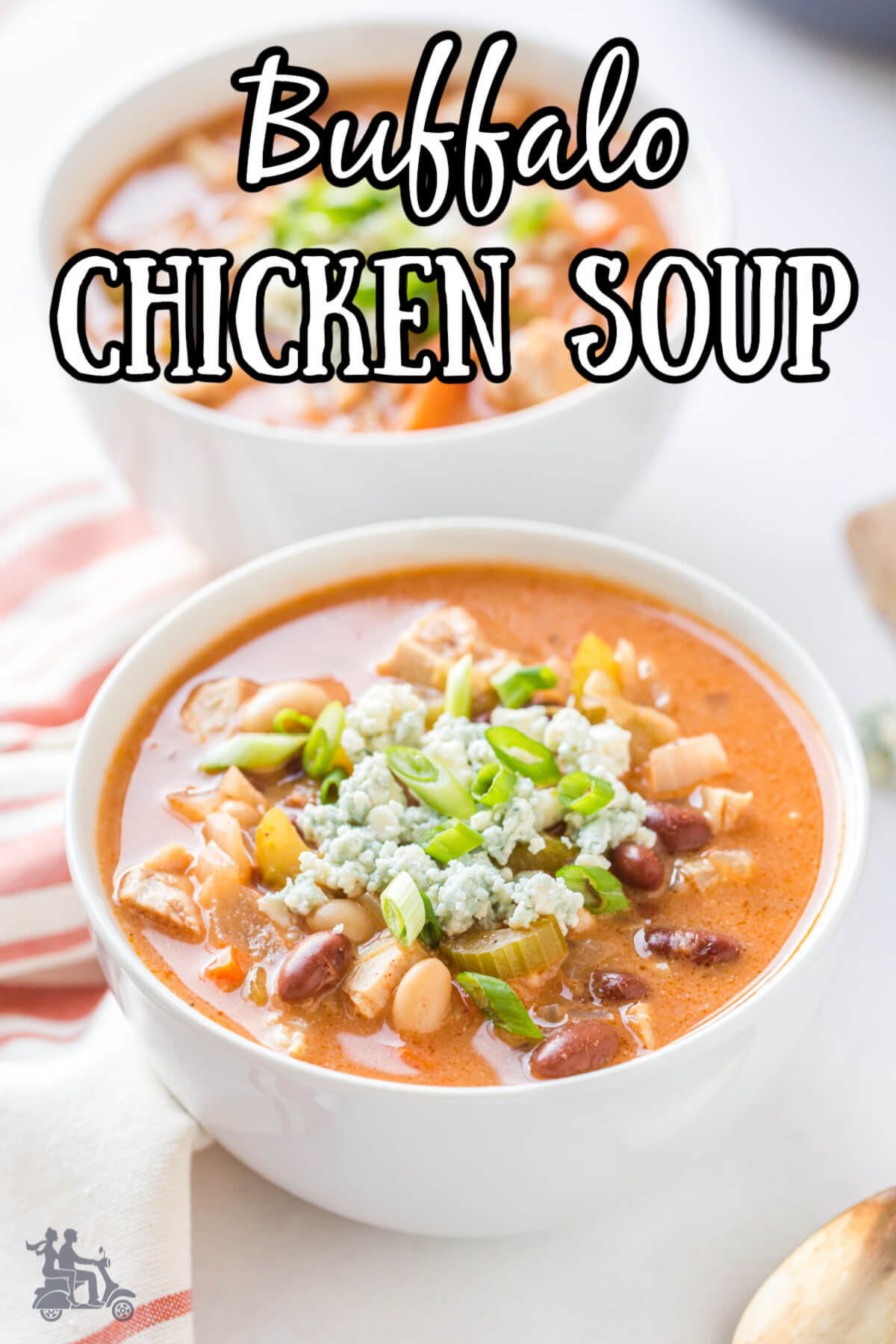 Two white bowls filled with Buffalo Chicken soup and garnished with bleu cheese and green onions.