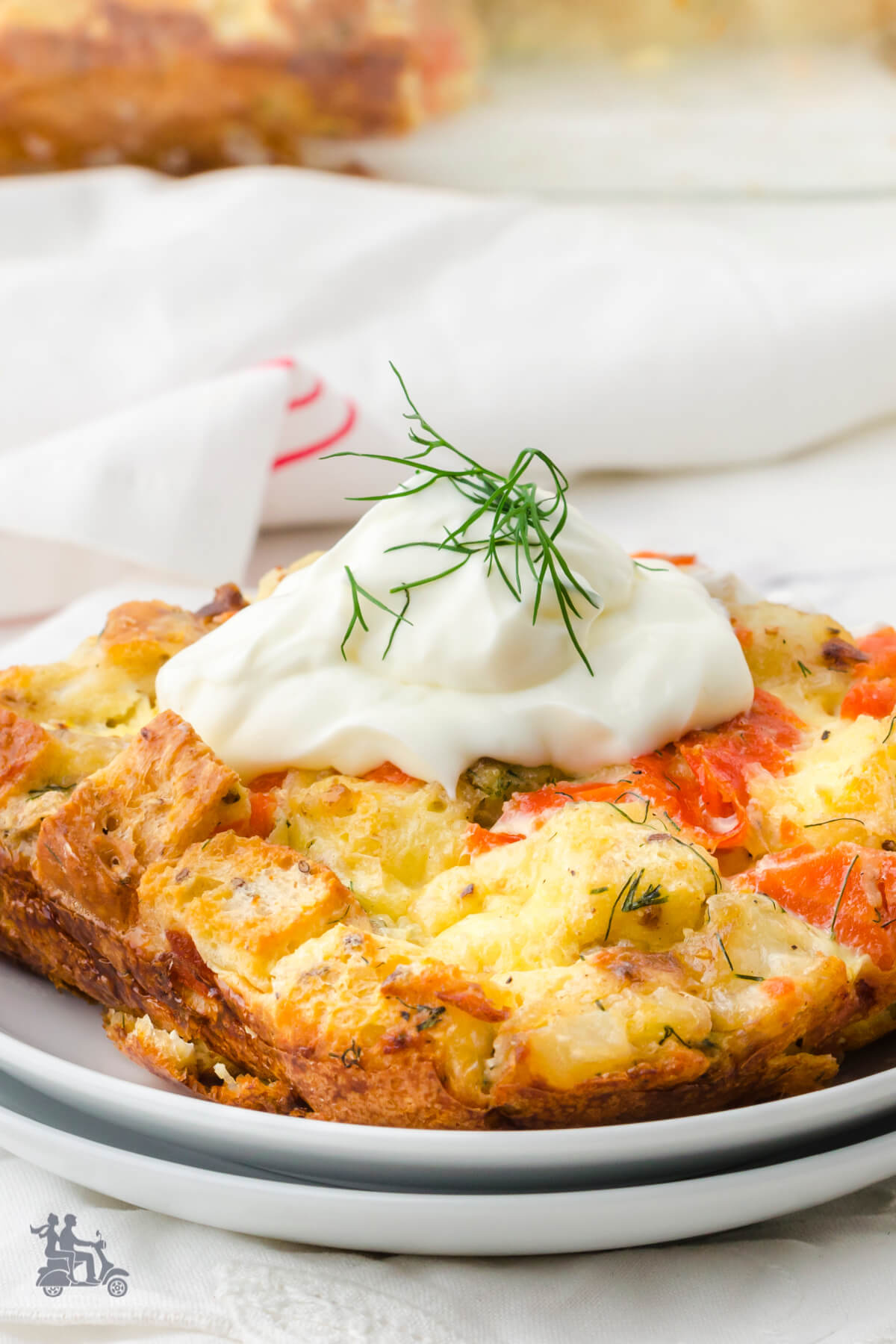 Salmon Egg Casserole Square with sour cream and dill on top.