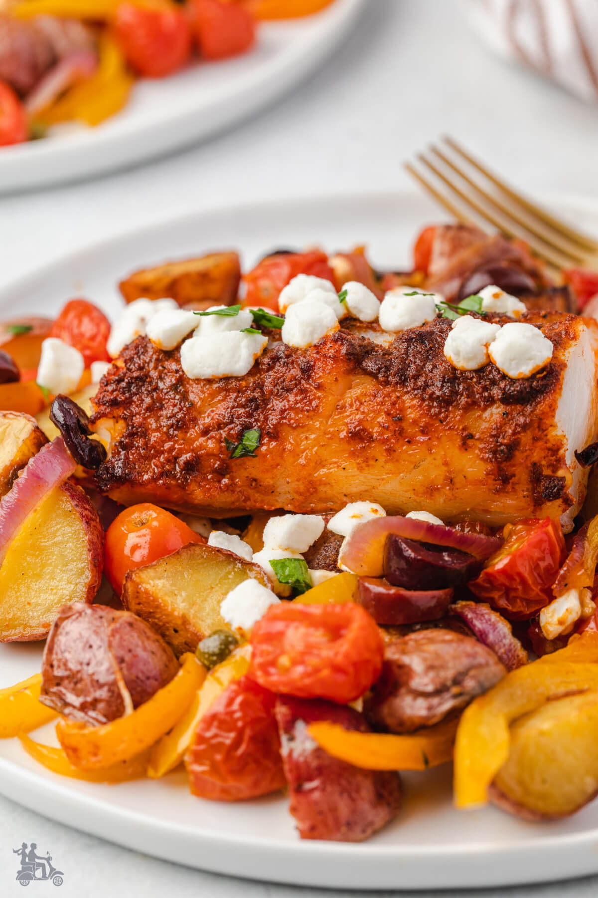 A serving of a baked cod fillet over roasted vegetables.